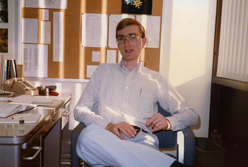 A young Rob Aanstoos from 1980 sits on a chair