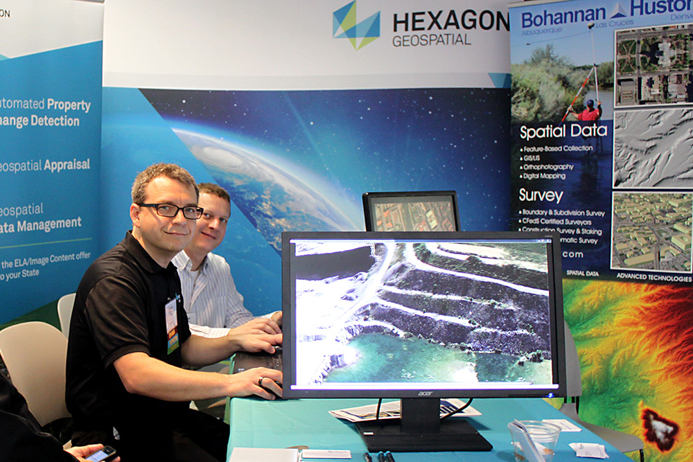 Two men smiling at hexagon geospatial booth