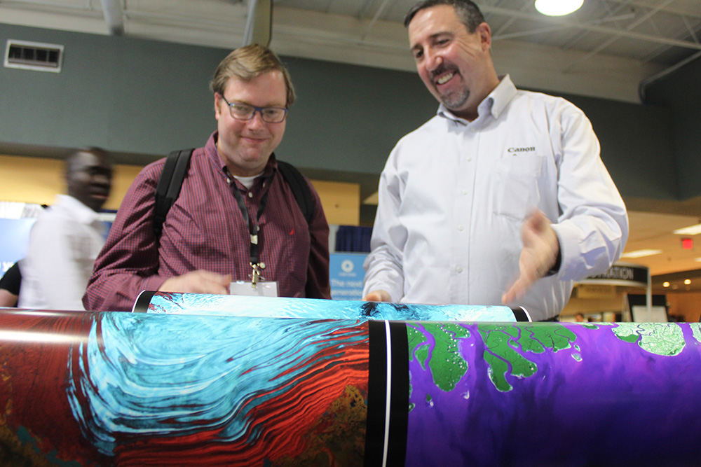 Plotter Pro, a Gold Sponsor, shows off their high-quality prints to a forum attendee.