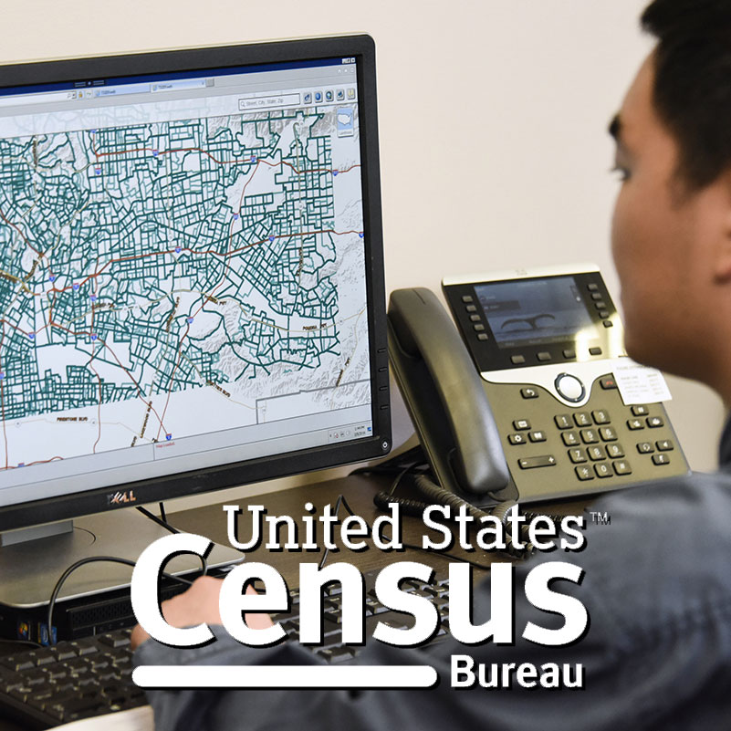 Person working on computer with GIS, US Census logo on top