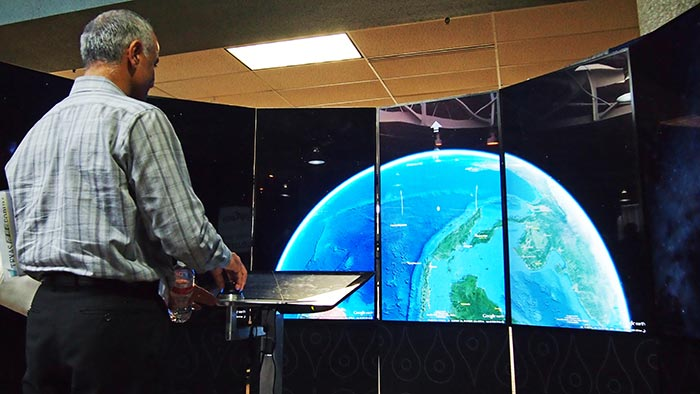 A man looks at a space view of the Earth on the liquid Galaxy