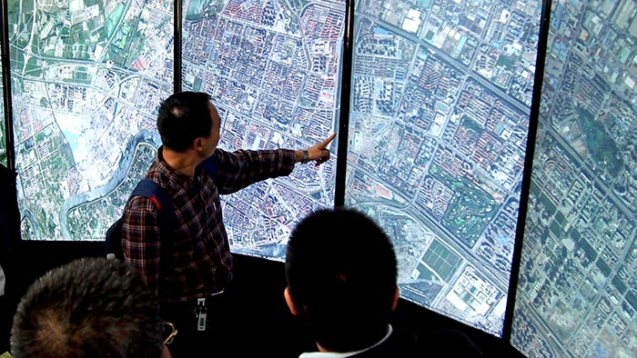 A man points out an area near his home in China on the liquid galaxy