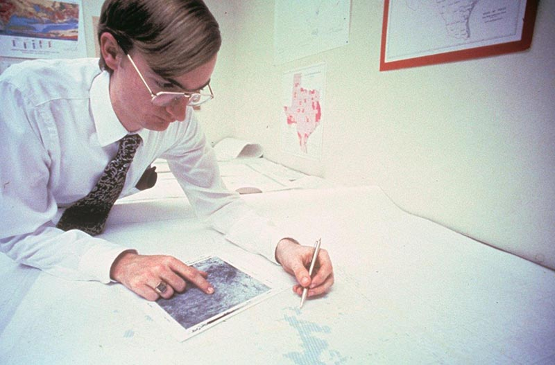 A picture from the 1980s, Rob is marking a plotted map and referencing an aerial photo