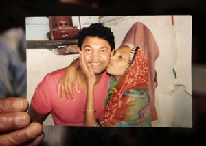 An image of hand holding photo of Saroo and his birth mother.
