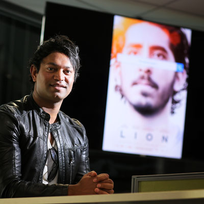 Image someone holding photo of Saroo Brierley being kissed by family member.