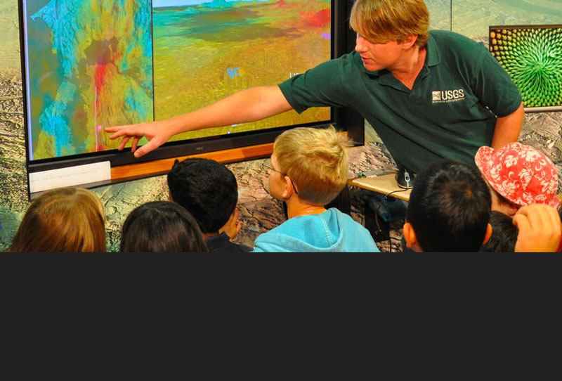 A USGS staff member shows kids a map
